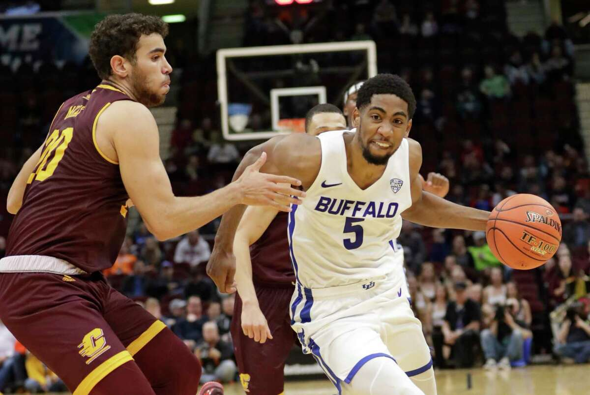 Buffalo's CJ Massinburg (5) drives past Central Michigan's Kevin McKay (20) during the second half of an NCAA college basketball game in the semifinals of the Mid-American Conference men's tournament Friday, March 15, 2019, in Cleveland. (AP Photo/Tony Dejak)