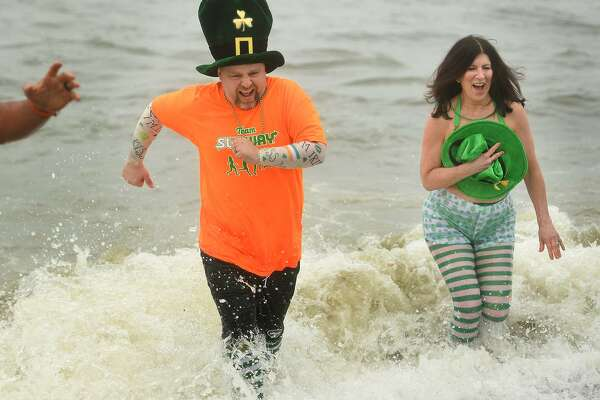 Team Subway members John Sinnott and Paula Kranyak, both of Milford, run from cold waters of the Sound during the Literacy Volunteers of Southern Connecticut's annual Leprechaun Leap at Walnut Beach in Milford, Conn. on Sunday, March 10, 2019.