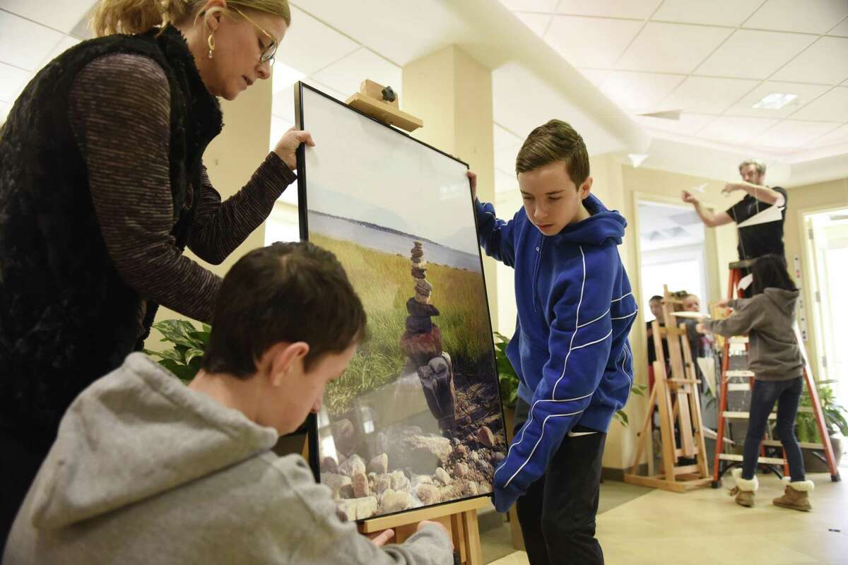 """Eastern Middle School art teacher Stacey Cleary and eighth-graders Luke McQuillan, center, and Nicholas O'Brien set up a photograph from Tod's Point for their art show """"A Line in the Sand"""" at First Bank of Greenwich in Cos Cob."""
