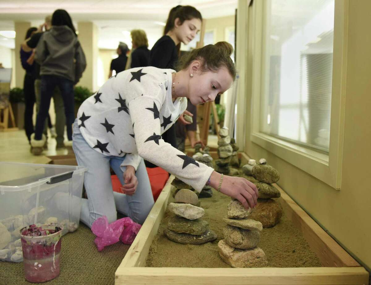 """Emily Phillipps sets up the rock garden for the student art show """"A Line in the Sand."""""""