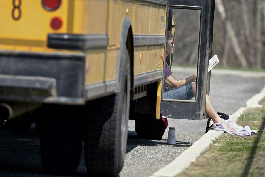 Priscilla Parzuchowski, a bus driver from First Student, reads a book and catches some sun. Photo: H John Voorhees III / Hearst Connecticut Media / The News-Times