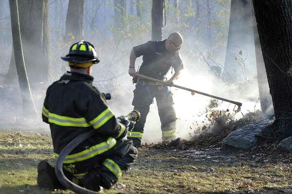 A four-acre brush fire, whipped by strong winds, ignited Friday afternoon, Nov. 11, 2016, near Ball Pond in New Fairfield and threatened several homes in Danbury before crews were able to get the blaze under control.
