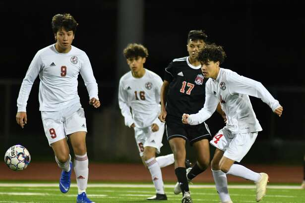 Cy Lakes sophomore Ulysses Jaimes (9) and junior Saul Gutierrez (4) team-up to clear the ball away from Langham Creek sophomore midfielder Carlos Huato (17) late in the 2nd period of their District 14-6A matchup at LCHS on Match 15, 2019.