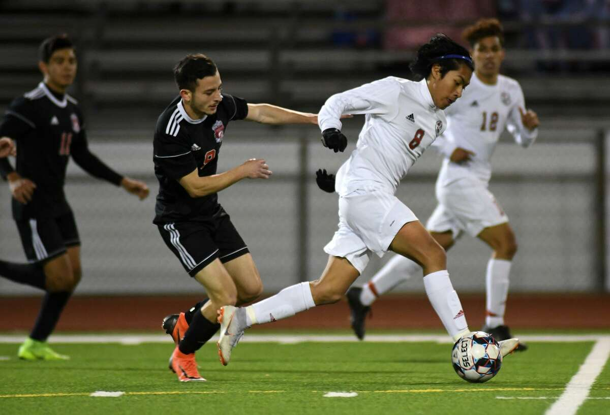 Cy Lakes junior Brandon Tuch, right, pushes the ball upfield against Langham Creek senior forward Emanuel Morales, left, during their District 14-6A matchup at LCHS on Match 15, 2019.