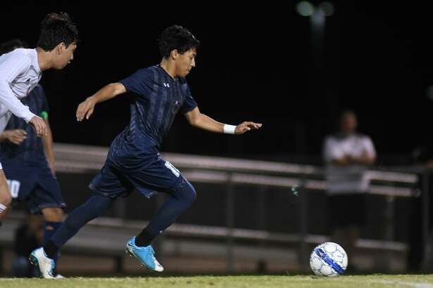 Tomball Memorial senior midfielder Edgar Chevez Gomez pushes the ball upfield ahead of Cy Lakes defender Marcus Rangel during their District 14-6A match at Tomball Memorial High School on Feb. 5, 2019.