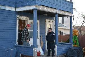 Ron Merriman escorted out of house by police Monday.