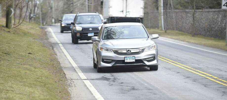 Drivers pass by potholes on North Street in Greenwich, Conn. on Friday, March 15, 2019. Photo: Matthew Brown / Hearst Connecticut Media / Stamford Advocate