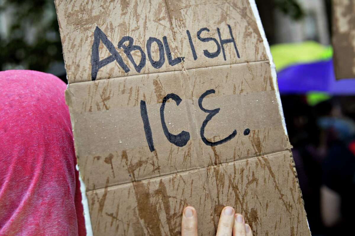 A demonstrator holds a sign that reads