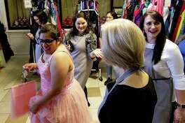 Aulce Saldier shares a laugh as she walks in her dress to get alterations during the annual Priceless Gowns event at First Baptist Church, Thursday, March 22, 2018, in Conroe.