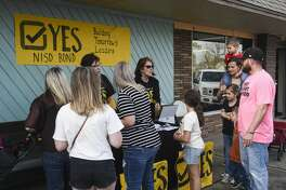 Phyllis Mosley, left, and Suzie Tweedel talk to people at a NISD Bond booth outside of Nederland's Heritage Festival on Tuesday. Photo taken on Tuesday, 03/12/19. Ryan Welch/The Enterprise