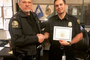 Lt. Louis Pannone presents a departmental commendation to Det. Sgt. Pier Corticelli, right.