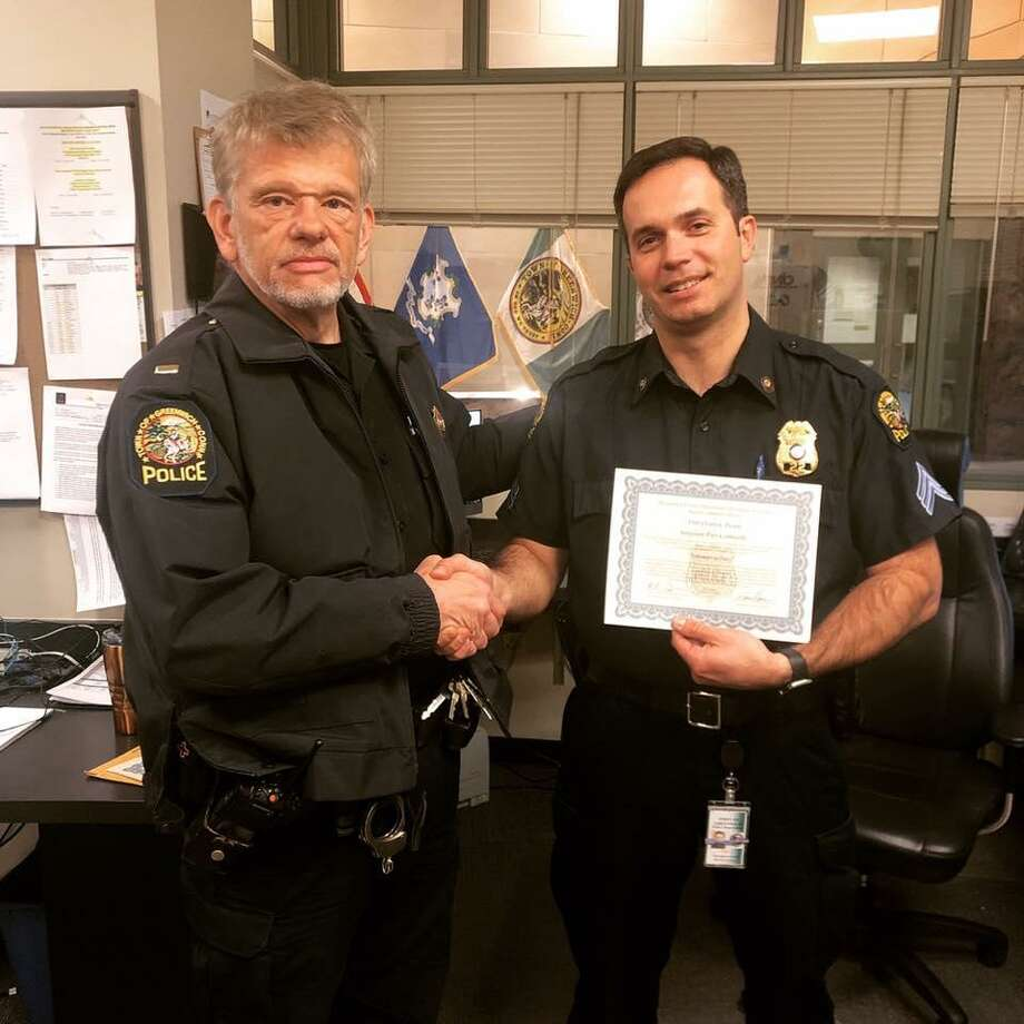 Lt. Louis Pannone presents a departmental commendation to Det. Sgt. Pier Corticelli, right. Photo: / Contributed