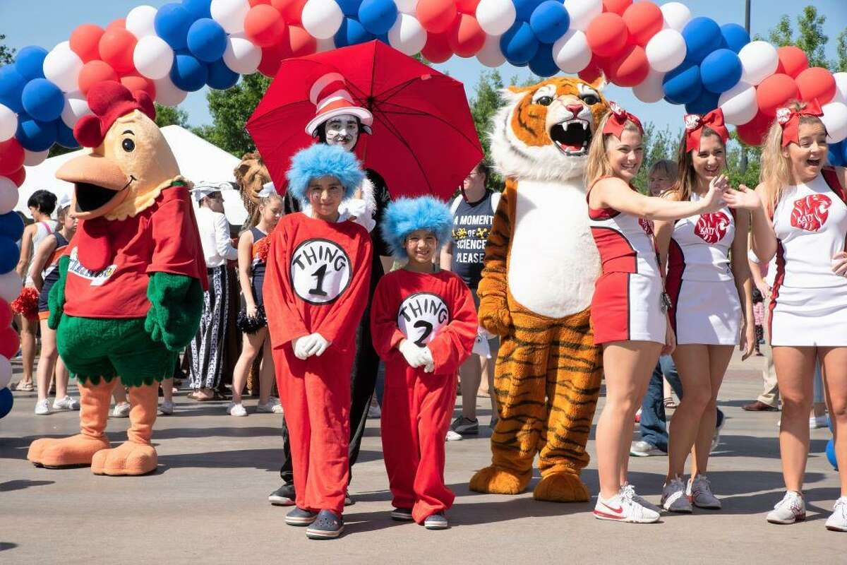 Katy cheerleaders join characters on display during the Fort Bend Arts Festival Storybook Character Parade.