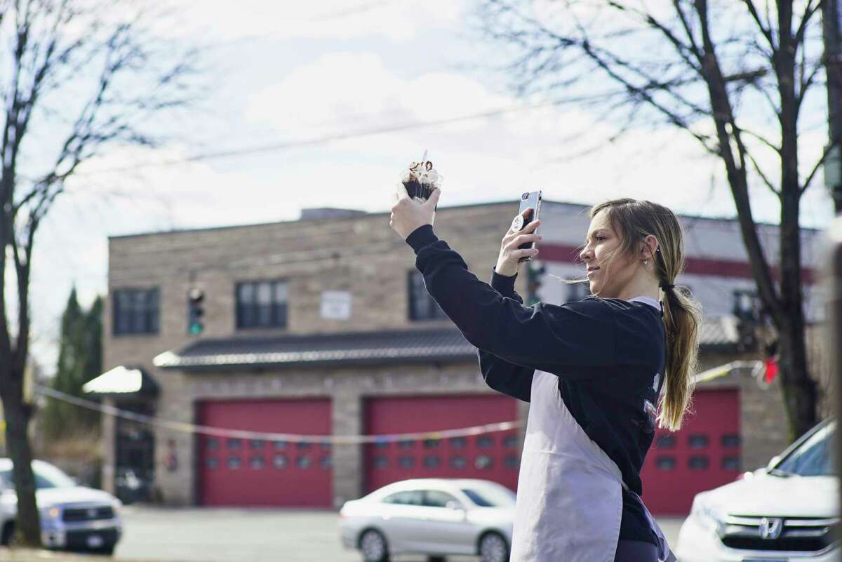 """March means time for ice cream in the Capital Region. See below for our list of seasonal ice cream stand opening dates. Employee Kaitlyn Plowman takes a photo for social media of the new """"Sweet and Salty"""" on opening day at Kurver Kreme on Monday, March 18, 2019, in Albany, N.Y. The """"Sweet and Salty"""" is made of ice cream, fudge, pretzels and whipped cream, with the extreme version adding either caramel or peanut butter to it. (Paul Buckowski/Times Union)"""