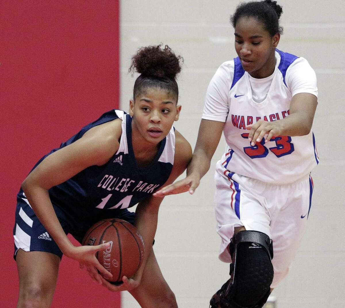 College Park's Sandra Cannady (14) protects the ball from the attempted steal by Oak Ridge North's Chelsea Cogborn (33) during the second half of their game at Oak Ridge North High School Friday, Dec. 14, 2018 in Oak Ridge North, TX.