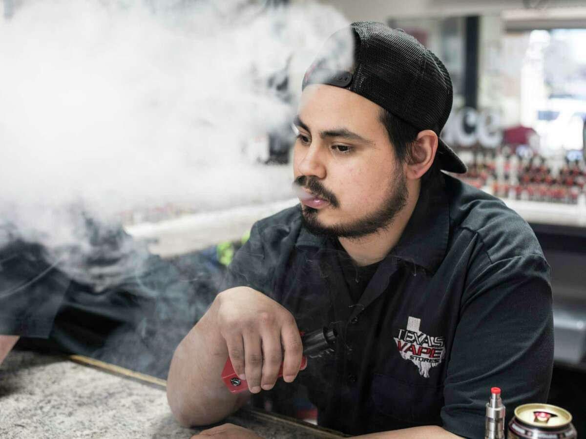 Employee Art Diaz uses his e-cigarette as he works at the Texas Vape Store off of Austin Highway on Monday, January 23, 2017 in San Antonio, Texas. A new poll found that most Texans would support new taxes on e-cigarettes and vaping products, as well as a state income tax on those who make more than $1 million a year.