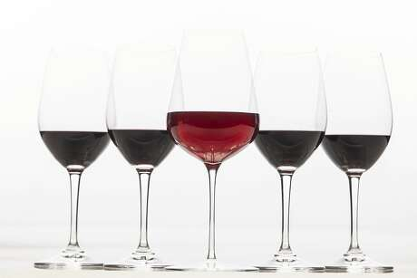 """A new trend in California wines is """"translucent reds"""" which are lighter and brighter than traditional reds. Here a glass of translucent red is seen with darker traditional reds on Thursday, March 14, 2019 in San Francisco, Calif."""