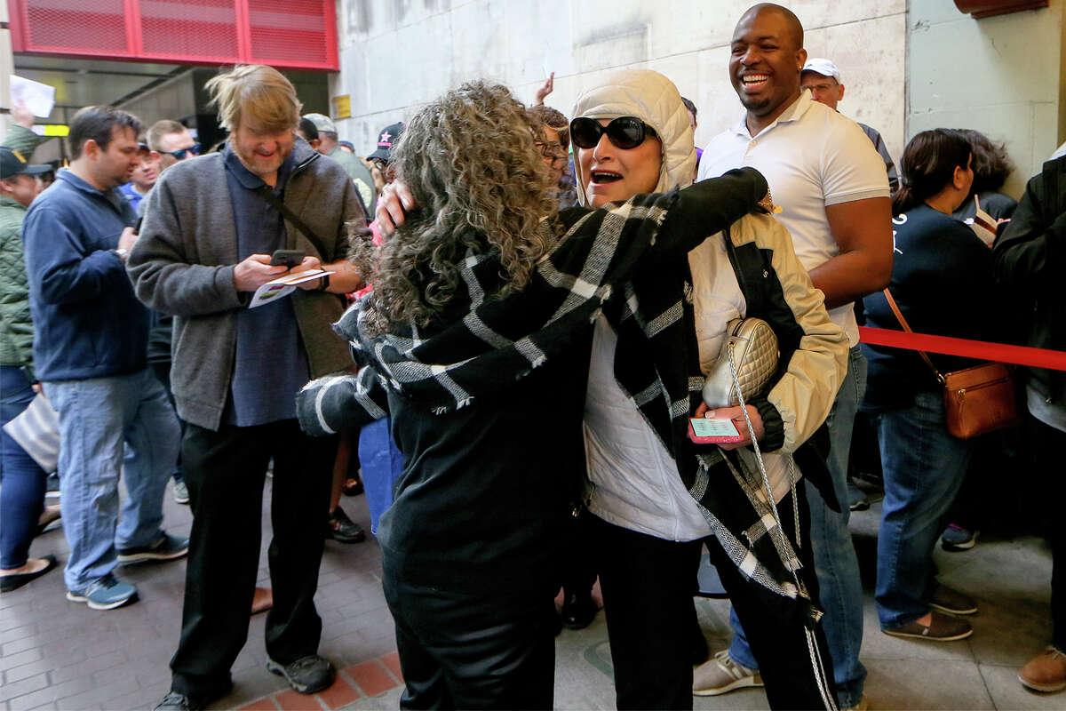 """Rochelle Lefton, front right, receives a congratulatory hug after drawing the first lottery number called, 7161, as people wait in line for tickets for """"Hamilton"""" to go on sale at the Majestic Theatre box office on Friday, March 15, 2019. Lefton was purchasing tickets to help celebrate her 45th wedding anniversary. Tickets were available online but a small number of tickets were available at the box office."""