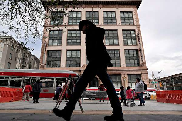 A man walks by a temporary bus platform in front of the old AMC Theater building on Van Ness Avenue in San Francisco, Calif., on Thursday, March 7, 2019. Morgan is a neighborhood activist who has been working on improving Van Ness for decades, and while California Pacific Medical Center has been recently completed, there are three developments that are stalled -- 1001 Van Ness, 1200 Van Ness, and the parking lot behind the Opal Motel.