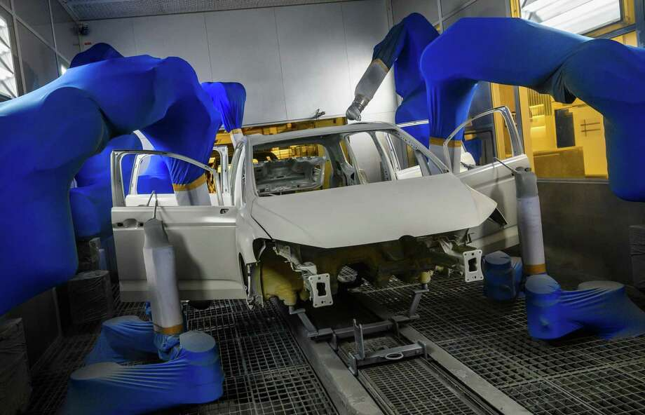 A Volkswagen car body is painted by robots on a production line at German car manufacturing giant Volkswagen's headquarters in Wolfsburg, northern Germany. Automation replacing workers is an old story but doesn't explain the wage stagnation of late. Photo: JOHN MACDOUGALL /AFP /Getty Images / AFP or licensors