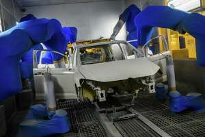 A Volkswagen car body is painted by robots on a production line at German car manufacturing giant Volkswagen's headquarters in Wolfsburg, northern Germany. Automation replacing workers is an old story but doesn't explain the wage stagnation of late.