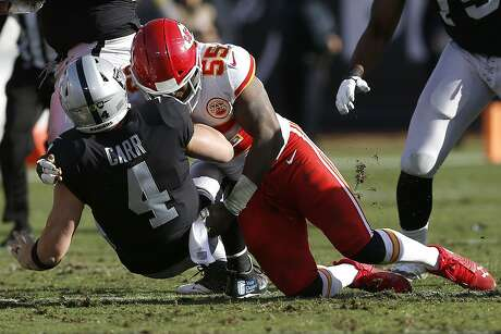 FILE - In this Dec. 2, 2018, file photo, Oakland Raiders quarterback Derek Carr (4) is tackled by Kansas City Chiefs linebacker Dee Ford (55) during the first half of an NFL football game in Oakland, Calif. The San Francisco 49ers opened the new league year Wednesday, March 13, by acquiring the defensive playmaker the team was sorely lacking in edge rusher Ford, as well as running back Tevin Coleman. The 49ers are sending a 2020 second-round pick to Kansas City for Ford and are giving him a new five-year contract, according to a person familiar with the deal who spoke on condition of anonymity because the trade hadn't been announced. (AP Photo/D. Ross Cameron, File)