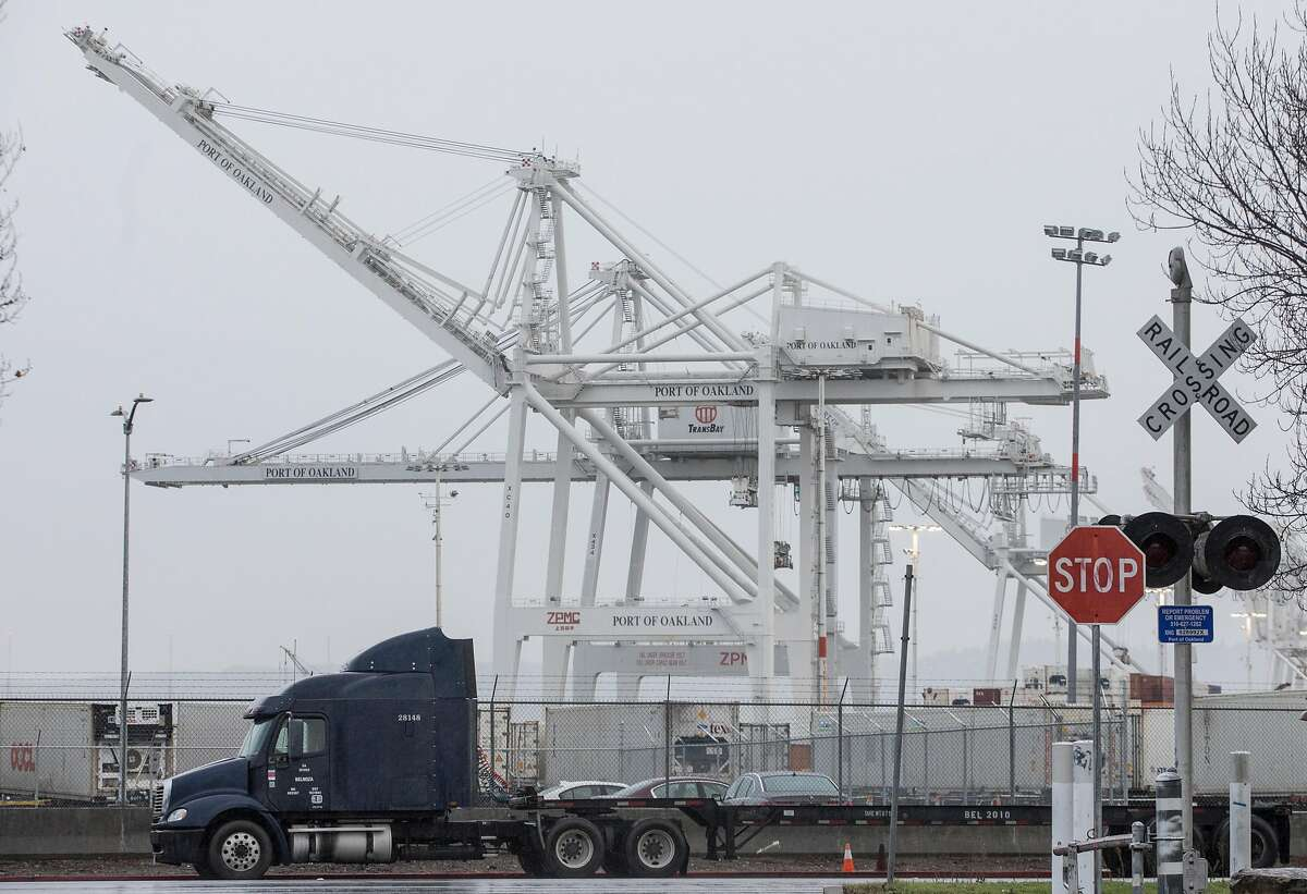 Trucks make their way through large cranes at the Port of Oakland in Oakland, Calif. Tuesday, Jan. 15, 2019.