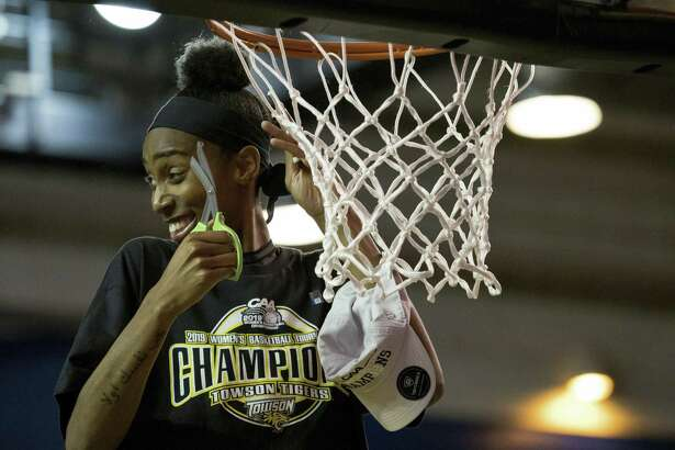 Towson forward Nukiya Mayo (1) cuts the net after their win in the Colonial Athletic Association championship.