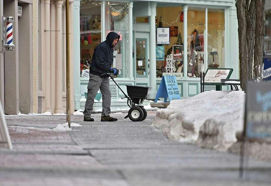 A man salts the sidewalks along River St. on Tuesday, Jan. 22, 2019 in Troy, N.Y. (Lori Van Buren/Times Union) Photo: Lori Van Buren / 40046013A