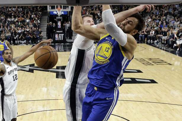 Golden State Warriors center Andrew Bogut (12) is hit across the face as he scores against San Antonio Spurs center Jakob Poeltl (25) during the first half of an NBA basketball game, in San Antonio, Monday, March 18, 2019. (AP Photo/Eric Gay)