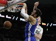 Golden State Warriors center Andrew Bogut (12) is hit across the face as he score against San Antonio Spurs center Jakob Poeltl (25) during the first half of an NBA basketball game, in San Antonio, Monday, March 18, 2019. (AP Photo/Eric Gay)