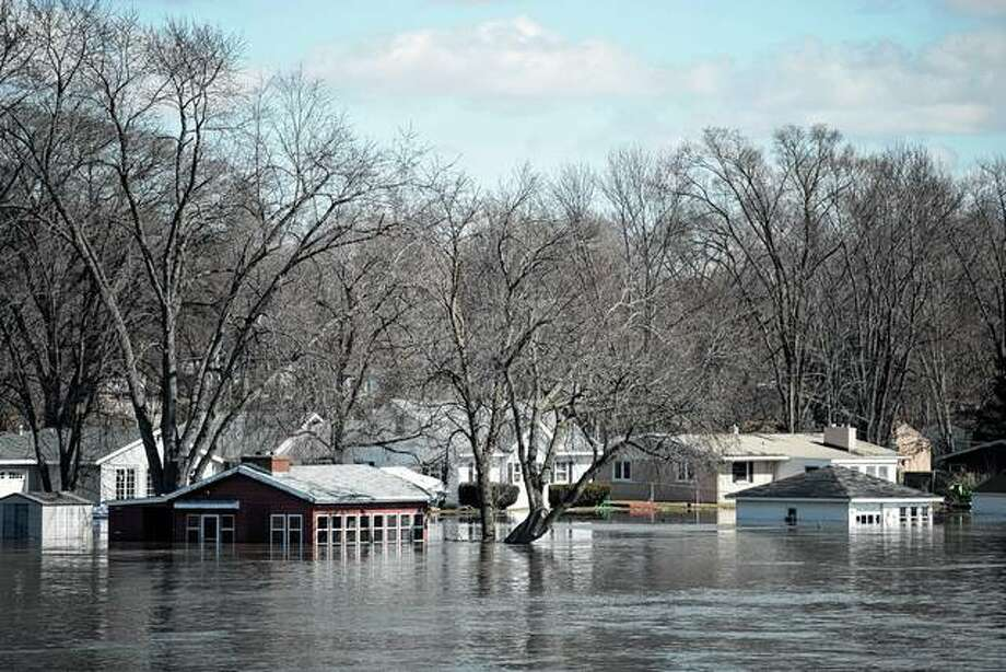 The Rock River floods Shore Drive on Saturday after cresting its banks in Machesney Park. Many rivers and creeks in the Midwest are at record levels after days of snow and rain. Photo: Scott P. Yates | Rockford Register Star Via AP
