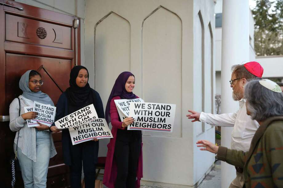 From left, Hudda Ibrahim, 17, Ranya Ibrahim, 15, and Gowiria Yousif, 15, hand out signs to people as they arrive at an interfaith vigil and anti-islamophobia teach-in at the Muslim Association of Puget Sound, held in response to last week's mass-shooting in Christchurch, New Zealand, Monday, March 18, 2019. Photo: Genna Martin / seattlepi.com