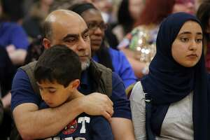 Nayab Khan holds his son after speaking about his friend, Naeem Rasheed, who was killed in last week's mass-shooting in Christchurch, New Zealand. Hundreds attended an interfaith vigil and anti-islamophobia teach-in at the Muslim Association of Puget Sound, held in response to the shooting, Monday, March 18, 2019.