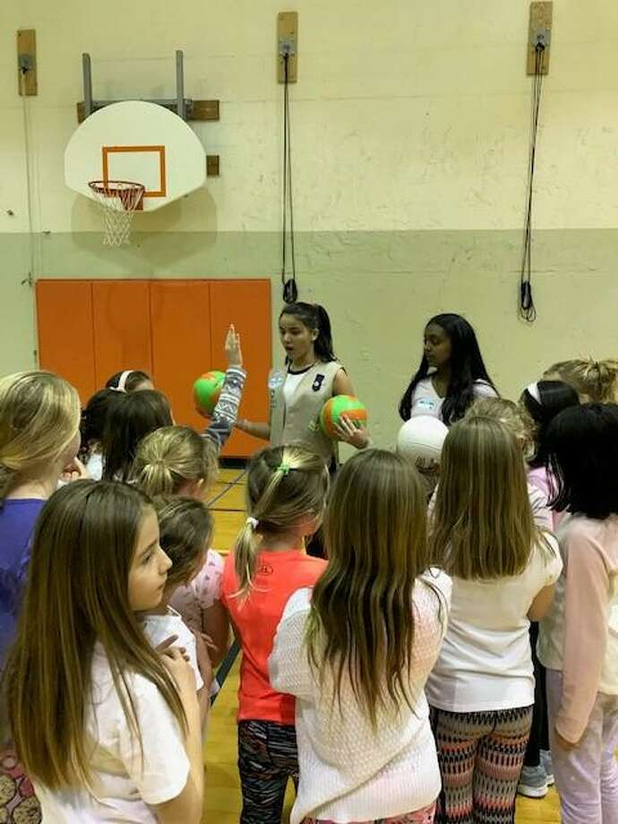 Audrey Mackay (left), and Neha Iyer (right), Greenwich High 9th graders of Troop 50540, prepare younger Girl Scouts to play a game their troop invented using volley balls, plastic soda bottles, and glow sticks. Photo: Contributed