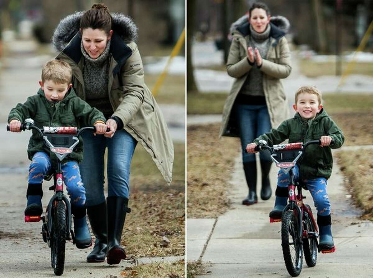Rachel Warner gives her son, Emmett Warner, 5, a push as he learns to ride his bike on Monday afternoon in front of their home in Midland. (Katy Kildee/kkildee@mdn.net)