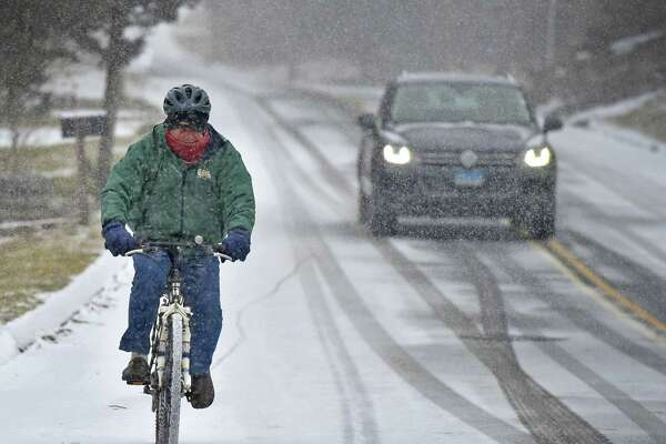 Branford, Connecticut - Tuesday, February 12, 2019: Trying to miss the snowfall earlier, Len Paolella of Branford rides his hybrid electric bicycle on Pine Orchard Road in Branford as the snow started Tuesday while returning from an errand in town. Paolella made the electric bicycle himself.
