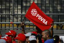 A pro-government supporter waves a flag displaying the Petroleos de Venezuela SA (PDVSA) logo at a rally Caracas, Venezuela, on Jan. 31, 2019. MUST CREDIT: Bloomberg photo by Marcus Bello.