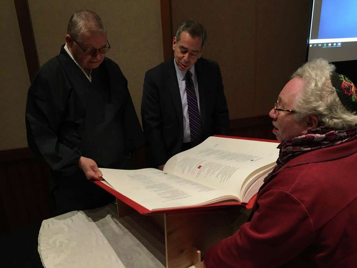"""Rev. Monshin Paul Naamon from the Tendai Buddhist Institute, extremism expert Mark Weitzman and Rabbi Beverly Magidson from the Jewish Federation of Northeastern New York,look at St. John's Bible at the College of Saint Rose before the annual Sidney and Beatrice Albert Interfaith Lecture on """"The New Face of Extremism"""" in Albany, N.Y. on Monday, March 18, 2019."""