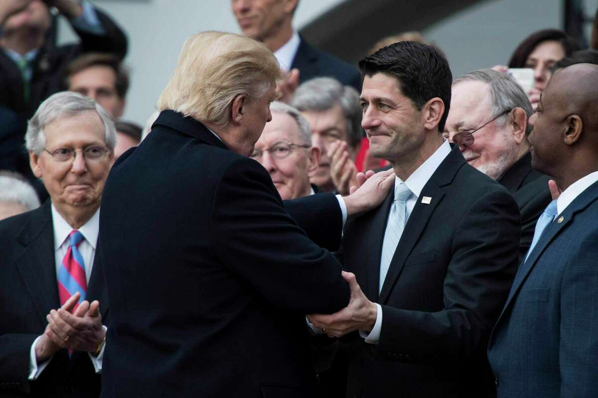 President Donald Trump embraces then-House Speaker Paul Ryan, R-Wis., during a news conference on the South Lawn of the White House on Wednesday, Dec. 20, 2017.