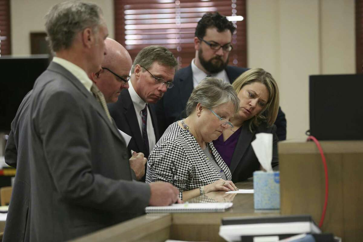 Attorney Phil Ross, left, watches as attorneys for the guardians of incapacitated Charlie Thrash, 81, and his estate, go over an order issued by Bexar County 73rd District Court Judge David A. Canales, during an adoption hearing, Tuesday, March 19, 2019. The guardians took Joe Martinez Thrash, 27, and his sister, Brittany Martinez Thrash, 25, to court to have their adoption by the elder Thrash nullified. Their mother, Laura Martinez, 54, married Thrash on March 4th and he adopted the two the day after the five-minute ceremony. The ruling by Canales nullified the adoptions. Guardian attorneys are from left, William Leighner, Les Katona, Laura A. Cavaretta, Barrett Shipp and Karen Andersen.