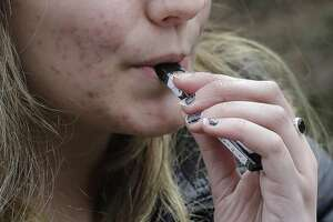 FILE - In this April 11, 2018 file photo, a high school student uses a vaping device near a school campus in Cambridge, Mass. Twice as many high school students used nicotine-tinged electronic cigarettes in 2018 compared with the previous year, an unprecedented jump in a large annual survey of teen smoking, drinking and drug use. Findings were released on Monday, Dec. 17, 2018. (AP Photo/Steven Senne, File)