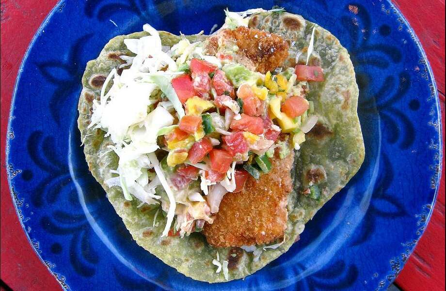 A deluxe fish taco on a tomatillo cilantro tortilla from the Austin-based Cabo Bob's Burritos, which is set to open a location in San Antonio. Photo: Mike Sutter /Staff File Photo
