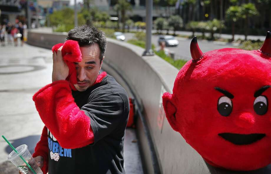Andrew Morales wipes sweat from his face while taking a break from his devil costume in Las Vegas in 2015 during record heat. Photo: John Locher / Associated Press 2015