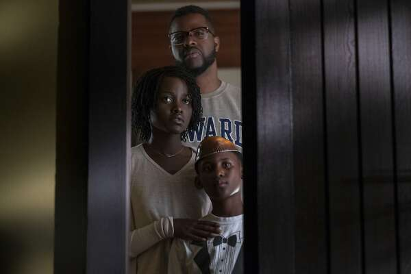 "This image released by Universal Pictures shows Winston Duke, Lupita Nyong'o and Evan Alex, right, in a scene from ""Us,"" written, produced and directed by Jordan Peele. (Claudette Barius/Universal Pictures via AP)"