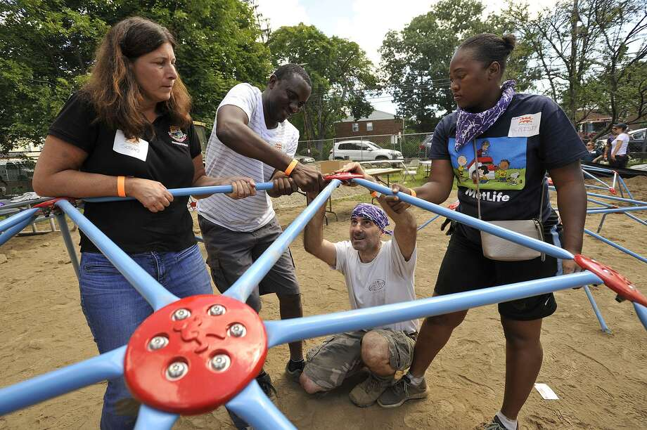 Susan Kisken, left, an engineer with the city, helps to assemble a jungle gym during a community effort to build a new playground at McKeithen Park in Stamford, Conn., on Friday, Aug. 28, 2015. The Board of Ethics has found probable cause that Kisken had a conflict of interest when she reviewed project plans submitted by a company that employs her husband. Photo: Jason Rearick / Hearst Connecticut Media / Stamford Advocate