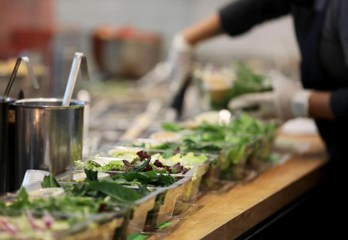 A Mixt employee assembles a row of salads in San Francisco. The local salad chain is continuing to grow in 2021, with new delivery-only locations.