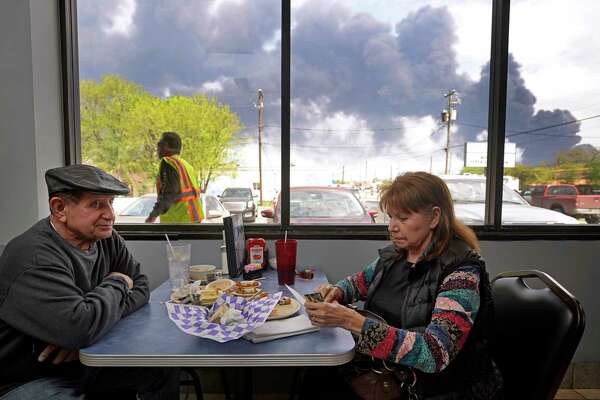 Charlie Tamez and his wife, Dalia Tamez, finish their lunch at Ken's Restaurant, 1122 Center St., as the chemical fire at Intercontinental Terminals Company continues to send dark smoke over Deer Park Tuesday, March 19, 2019. She said they eat at the Ken's often and it is usually packed for lunch, but today's crowd was sparse.