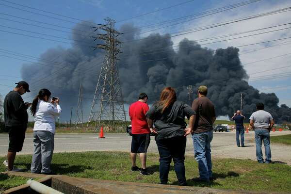 People gather to watch as firefighters continue to battle the petrochemical fire at Intercontinental Terminals Company, which grew in size due to a lack of water pressure last night, Tuesday, March 19, 2019, in Deer Park, Texas.