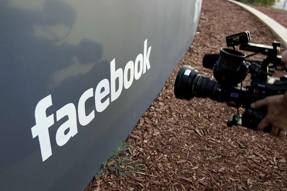 A television photographer shoots the sign outside of Facebook headquarters in Menlo Park. The company has settled five lawsuits over alleged discrimination in its ads. Photo: Paul Sakuma / Associated Press 2012